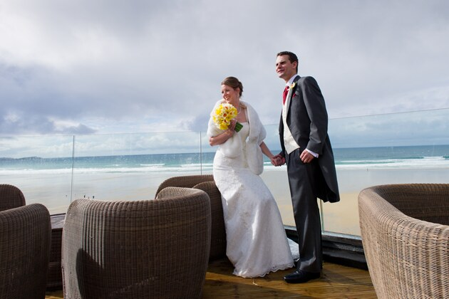 bride and groom with Watergate Bay beach backdrop
