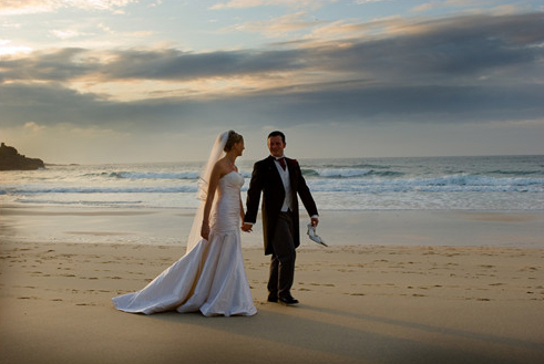 bride and groom stroll along a beach at St Ives