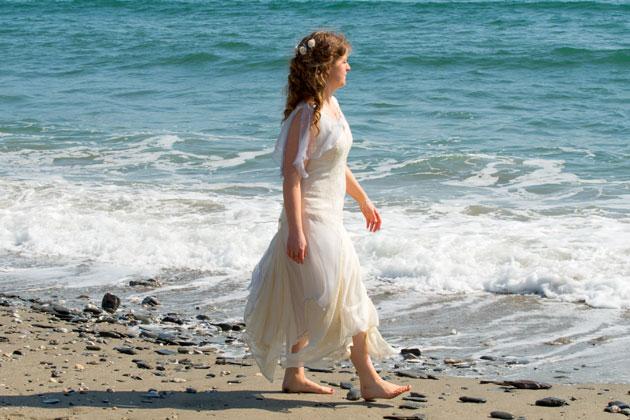 reportage bridal beach wedding photograph as bride strolls along the Cornish beach