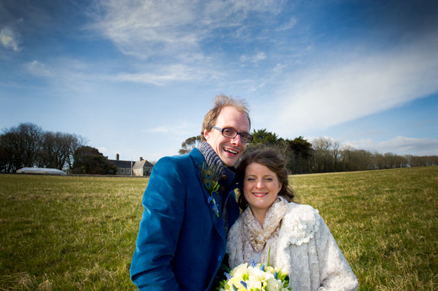 Bride and groom with wedding venue in background