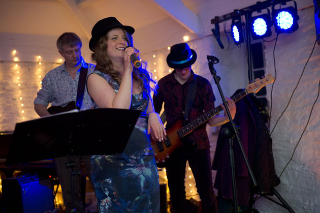 bride and groom with their band entertain their wedding guests
