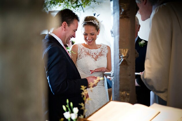 Wedding ceremony Porthilly Church Rock groom puts wedding ring on brides finger