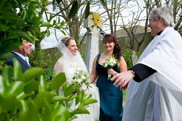 Wedding photograph of vicar welcoming the bride for her wedding at St Michael's church Porthilly Rock