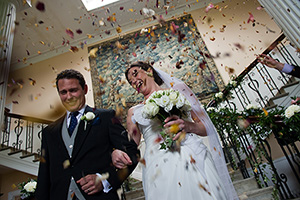 bride and groom being showered with confetti at Scorrier House after the wedding ceremony
