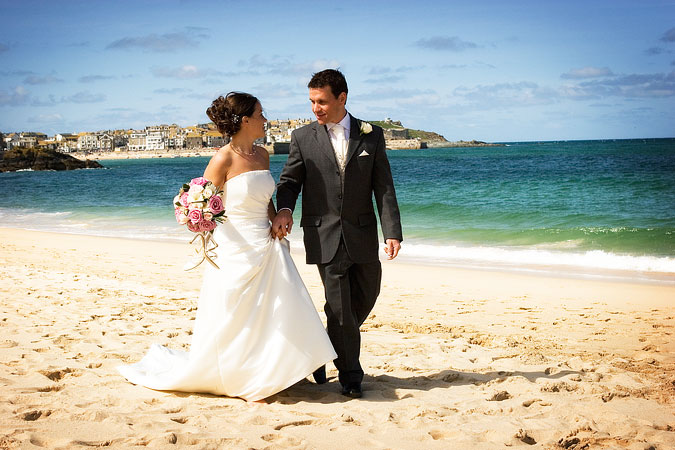 photograph by Shah Photography of bride and groom walking along Porthminster beach at St Ives in Cornwall