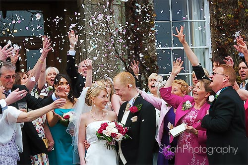 confetti being scattered over the newly weds