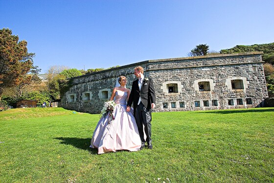 The bride and groom with Polhawn Fort in the background