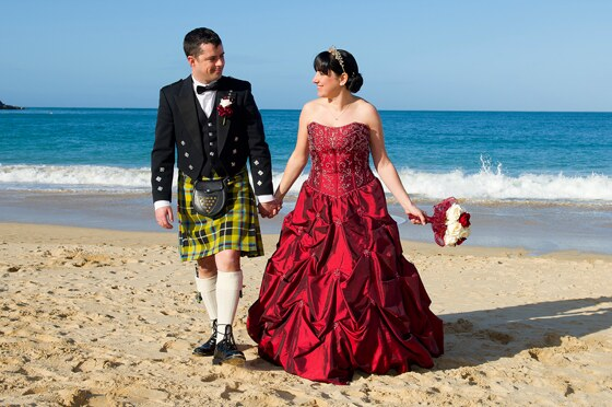 Bride and groom enjoy a stroll on Carbis Bay beach in glorious Cornish sunshine