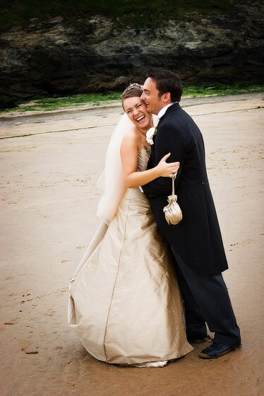 Bride and groom enjoying a beach photo session during their wedding day