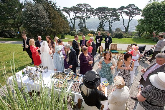 wedding guests enjoy the setting of Fowey Hall grounds