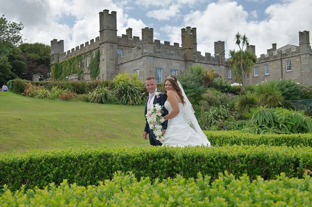 the bride and groom with backdrop of wedding venue Tregenna Castle