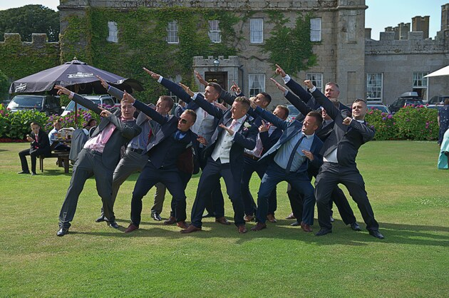 groom and groomsmen strike a pose infront of Tregenna Castle