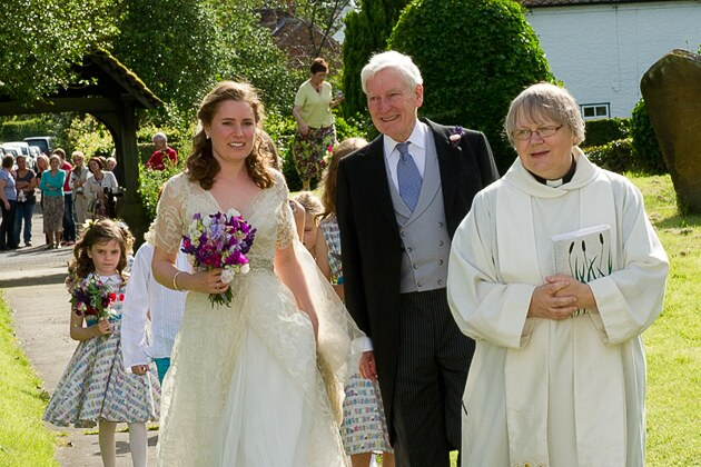 the arrival of the bridal party led by the vicar