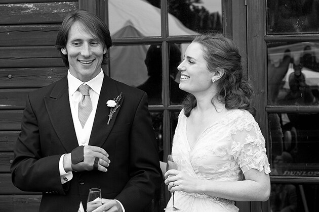 relaxed bride and groom smiling during the speeches