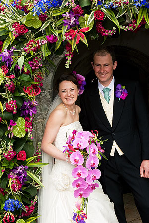 Anna and Ollie after their wedding ceremony photographed in the doorway of the church entrance with beautiful wedding flowers by Anna who is a top wedding florist in Cornwall