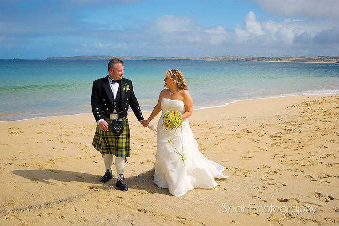 After their wedding ceremony, bride and groom, photographed walking along Carbis bay beach