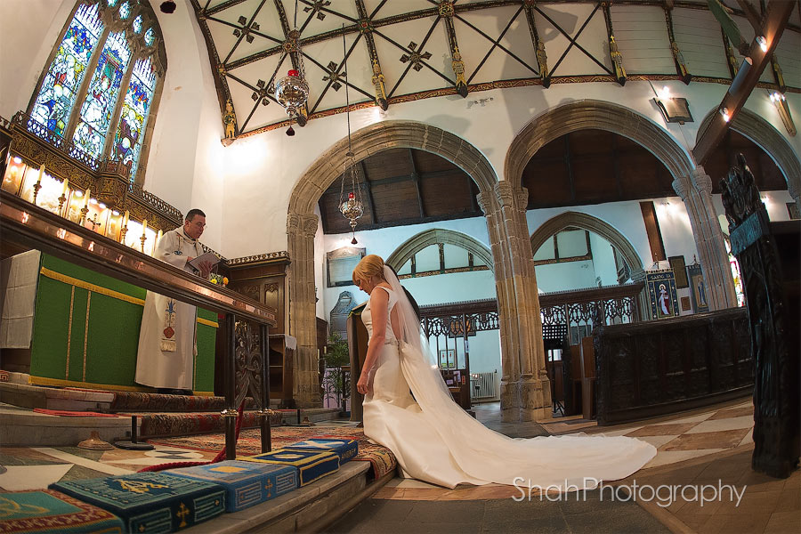 The bride and groom photographed kneeling at the alter during a prayer at St Ives Parish Church